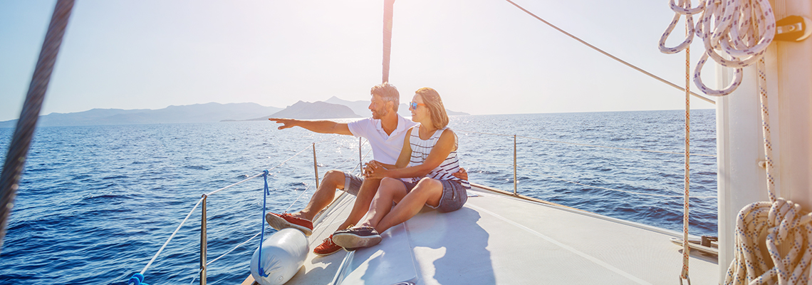 Man and woman pointing at something from sail boat